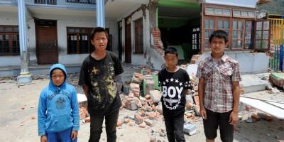 Zdjęcie pochodzi ze strony UNICEF i przedstawia nepalskie dzieci na tle szkoły zniszczonej przez trzęsienie ziemi